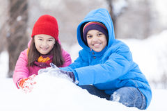 Boy and girl playing with snow outside. Stock Photo