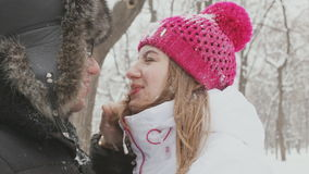 Boy and girl playing with snow in snow-covered park stock video footage