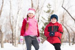 Boy and girl playing with snow in winter park Royalty Free Stock Photos
