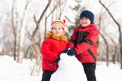 Boy and girl playing with snow in winter park Stock Photo
