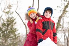 Boy and girl playing with snow in winter park Stock Photography