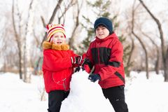 Boy and girl playing with snow in winter park Royalty Free Stock Photo