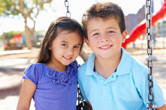 Boy And Girl Playing On Swing In Park. Smiling Royalty Free Stock Image