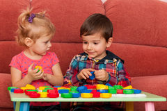 Boy and girl playing at the table stock photography