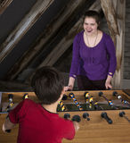 Boy and girl playing at table football Stock Image