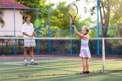 Child playing tennis on outdoor court Stock Image