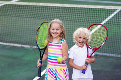 Children playing tennis on outdoor court Royalty Free Stock Photos