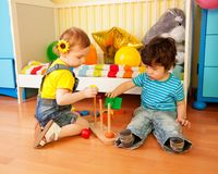 Boy and girl playing with toy pyramid puzzle Stock Photo