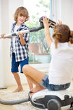 Boy and girl playing with vacuum cleaner Stock Photos