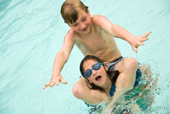 Boy and Girl Playing in the Water. A young boy and girl clowning around in the water. Nine years old stock photo