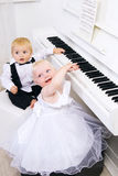 Boy and girl playing on a white piano Royalty Free Stock Photography