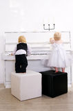 Boy and girl playing on a white piano. Boy and girl playing in a concert dress on a white piano royalty free stock image