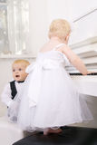 Boy and girl playing on a white piano Stock Images