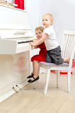 Boy and girl playing on white piano Royalty Free Stock Photography
