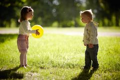 Boy and girl playing with yellow ball Stock Photos