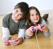 Boy and girl playstation. Young boy and girl playing with playstation together Stock Images