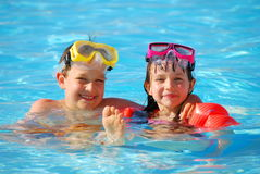 Boy and Girl in Pool. Happy young boy and girl floating in a pool Stock Photos