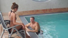 Boy and girl are in the pool. The guy and the girl are in the pool, the guy in the water, the girl is sitting in a shizlong on the board stock video
