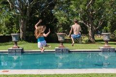 Boy Girl Pool Jumping. Boy girl teenagers jumping playing in swimming pool summer Stock Photos