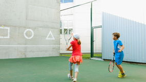 Boy and girl practiced tennis. Kids use the wall for training