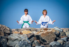 Boy and girl practising yoga on beach Royalty Free Stock Images
