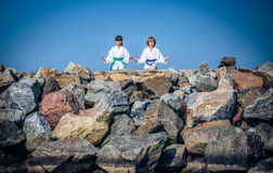 Boy and girl practising yoga on beach Stock Image