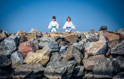 Boy and girl practising yoga on beach Stock Image