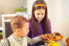 Boy and girl preparing and eating healthy meal at home Royalty Free Stock Images