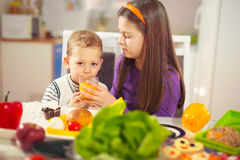 Boy and girl preparing and eating healthy meal at home Royalty Free Stock Image