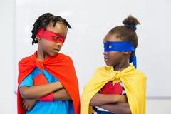 Boy and girl pretending to be a superhero. Boy and girl looking at each other and pretending to be a superhero Stock Photos