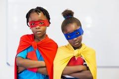 Boy and girl pretending to be a superhero Stock Photos