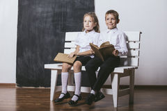 Boy and girl from primary school class on the bench read books o Royalty Free Stock Image