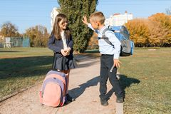 Boy and girl, primary school students with backpacks go to school. Sunny day background, road in the park.  royalty free stock photo