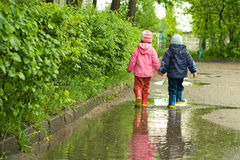 Boy and girl in the puddle Royalty Free Stock Photo
