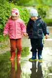 Boy and girl in the puddle Royalty Free Stock Photos