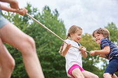 Boy and girl pulling a rope. And playing tug of war at the park Royalty Free Stock Image