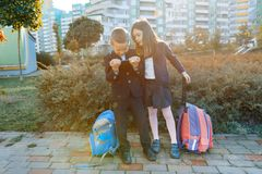 Boy and girl pupils in primary school with a digital tablet. Outdoor background, children with school bags, look at the tablet. Ed stock photos