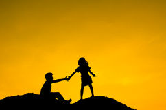 Boy and Girl raising her hands standing on top Royalty Free Stock Image