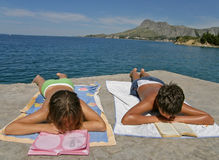 Boy and girl read at beach Stock Image