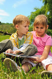 Boy and girl are reading a book Stock Images