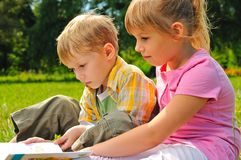 Boy and girl are reading a book Royalty Free Stock Photography