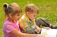 Boy and girl are reading a book Royalty Free Stock Image