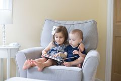 Boy and girl reading a book stock photography