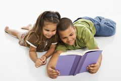 Boy and girl reading book together. Stock Photos
