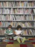 Boy And Girl Reading Books In Library Royalty Free Stock Image