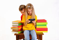 Boy and girl reading e-book surrounded by books