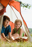 Boy and girl reading in a tent Royalty Free Stock Image