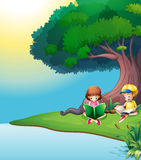 A boy and a girl reading under the tree Stock Photos