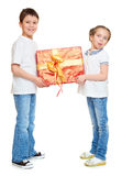 Boy and girl with red gift box and golden bow - holiday object concept isolated Royalty Free Stock Photos