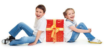 Boy and girl with red gift box and golden bow - holiday object concept isolated Stock Photography
